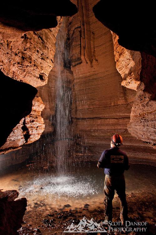 A single flash illuminates an underground waterfall.