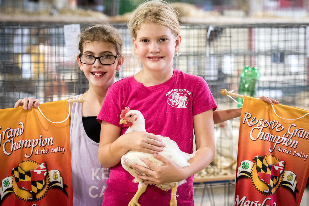 Timonium, Maryland - young girls pose with their champion banners and a small chicken at the 2016 Maryland State Fair.