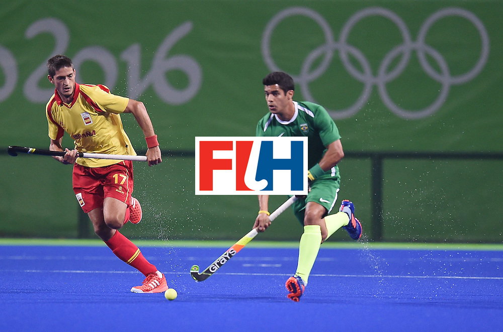 Spain's Xavi Lleonart (L) chases Brazil's Stephane Smith during the men's field hockey Spain vs Brazil match of the Rio 2016 Olympics Games at the Olympic Hockey Centre in Rio de Janeiro on August, 6 2016. / AFP / MANAN VATSYAYANA        (Photo credit should read MANAN VATSYAYANA/AFP/Getty Images)