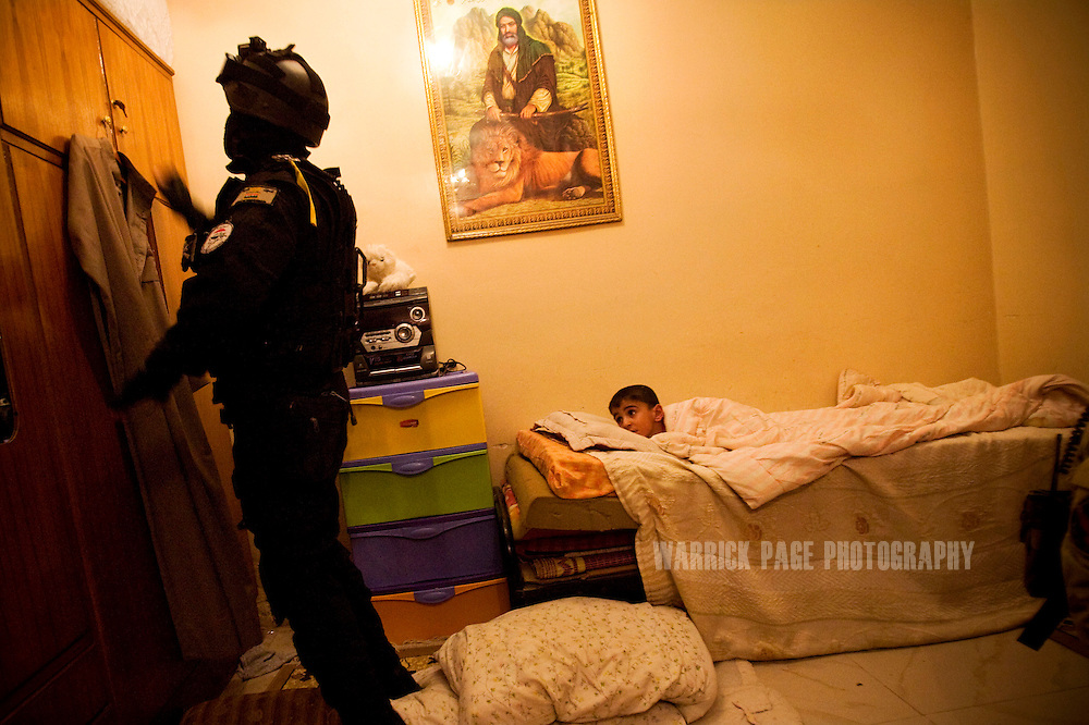 BAGHDAD, IRAQ - MAY 27: An Iraqi boy watches an Iraqi Emergency Response Brigade (ERB) member search his family home after an arrest warrant was issued for his father who was suspected for planting IEDs, on May 27, 2010, on the outskirts of Baghdad, Iraq. Iraqi Special Forces and ERB and been training under US Special Forces for several years with a heavy focus on evidence collection and both legal and human rights for detained suspects. Members of the unit make little more than $700 a month and keep their identity a secret as many prevail from areas where insurgency is rife. US Special Forces are not permitted to accompany Iraqi ERB on missions unless an arrest warrant has been issued. Iraq faces multiple challenges in the lead-up to the drawn-down of US forces in Iraq, with many observers claiming that while they have the capablities of handling home-grown problems, they are far from being able to tackle external threats. Political wrangling has reportedly fostered greater instability throughout the country with fears of renewed sectarian violence breaking out as insurgents set-up attacks in an attempt to exploit vulnerabilities amongst the populace. (Photo by Warrick Page)