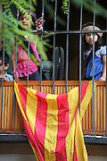 Pakistani girls behind a balcony and waving red and yellow striped Catalan flags for Catalan National Day on September 11, 2012, Barcelona, Spain. The severity of the worst economic crisis has fuelled separatism and highlighted fractures between Spain's northeast and the central government in Madrid. National Day, or Diada, in fact, marks the defeat of Catalan forces on September 11, 1714, at the hands of Philip V of Spain after a 13-month siege of Barcelona. Picture by Manuel Cohen