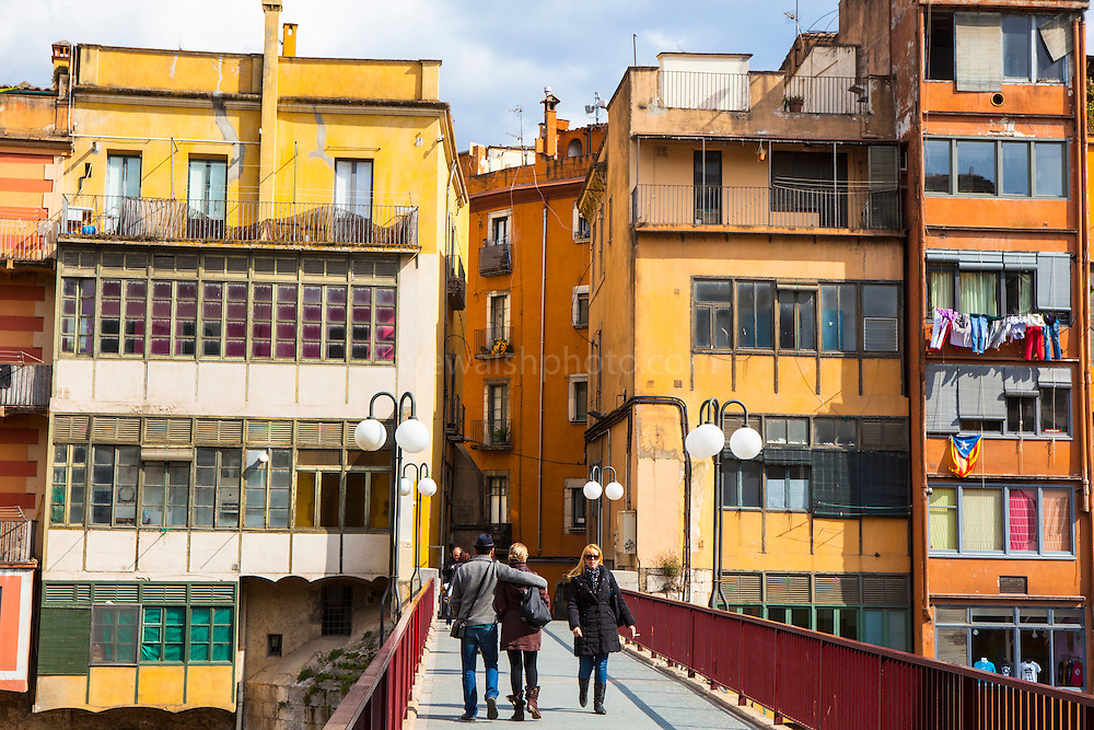 People crossing bridges surrounded by colourful buildings along the river Onyar, in Girona, Catalonia, Spain
