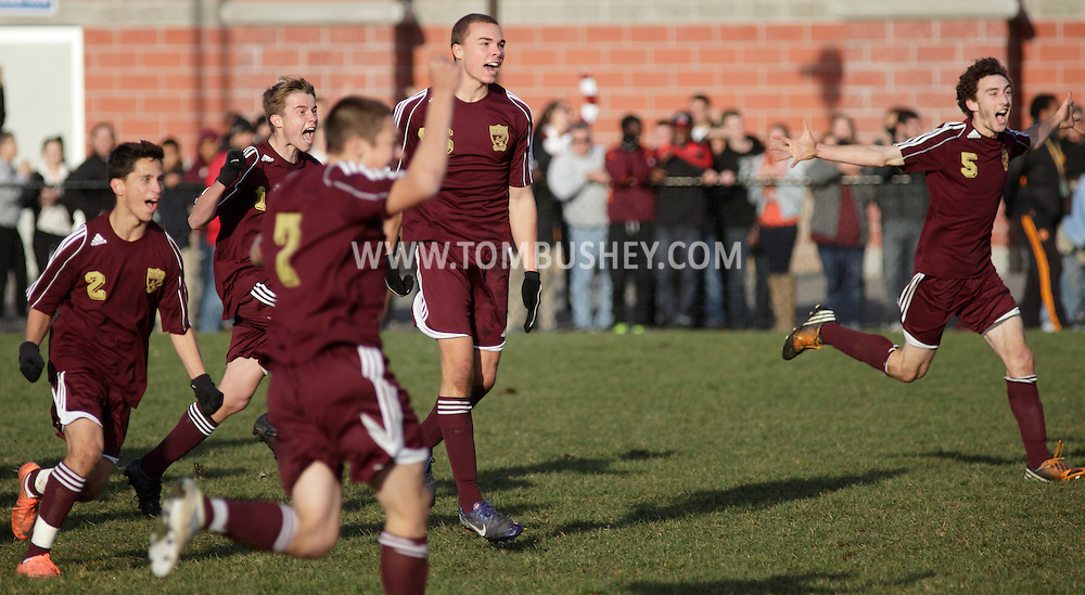 Arlington boys' soccer players celebrate their 2-1 victory over Brentwood in the Class AA state championship game at Faller Field in Middletown on Nov. 18, 2012.