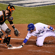 Kansas City Royals Alex Gordon doubled to score teammate Billy Butler who was safe at home plate before the tag of San Francisco Giants catcher Buster Posey during the second inning in Game 7 of the World Series on Wednesday, October 29, 2014 at Kauffman Stadium in Kansas City, Mo.