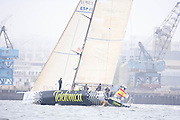 Telefonica Black sailing past the commercial port at the start of the Volvo Ocean Race, Leg 7, Boston.