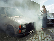 Young man standing in front of a van smoking.