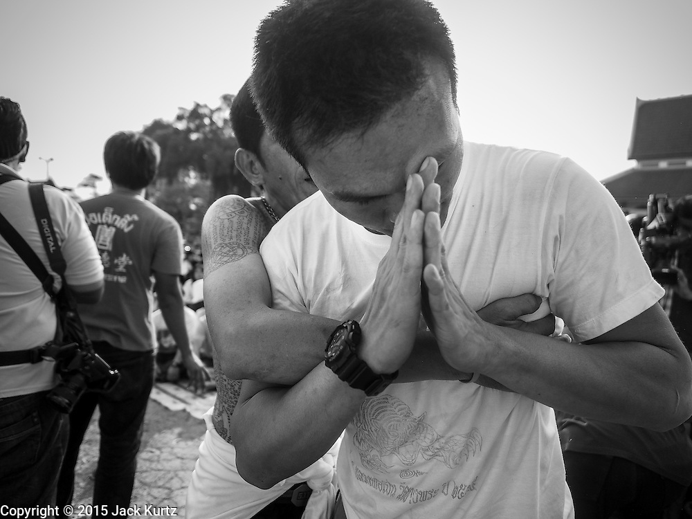 """07 MARCH 2015 - NAKHON CHAI SI, NAKHON PATHOM, THAILAND: A man prays after rushing the stage at the Wat Bang Phra tattoo festival. Wat Bang Phra is the best known """"Sak Yant"""" tattoo temple in Thailand. It's located in Nakhon Pathom province, about 40 miles from Bangkok. The tattoos are given with hollow stainless steel needles and are thought to possess magical powers of protection. The tattoos, which are given by Buddhist monks, are popular with soldiers, policeman and gangsters, people who generally live in harm's way. The tattoo must be activated to remain powerful and the annual Wai Khru Ceremony (tattoo festival) at the temple draws thousands of devotees who come to the temple to activate or renew the tattoos. People go into trance like states and then assume the personality of their tattoo, so people with tiger tattoos assume the personality of a tiger, people with monkey tattoos take on the personality of a monkey and so on. In recent years the tattoo festival has become popular with tourists who make the trip to Nakorn Pathom province to see a side of """"exotic"""" Thailand.   PHOTO BY JACK KURTZ"""