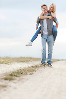 Full length of cheerful young man piggybacking woman on trail at field