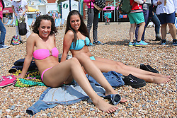 © Licensed to London News Pictures. 12/07/2014. Brighton, UK. 2 woman sunbathing on the beach. With temperatures around the 23C down the South Coast thousands of people taking a weekend away down on the beach. Photo credit : Hugo Michiels/LNP