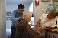 Ruthie receives a haircut from Mickey, who volunteers his professional skill regularly, at a live-in residence for Alzheimer's and dementia related  patients.