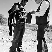 Rancher Jim Chilton offers water to Ivan Rebollar, 15, who said he'd been walking for two days without food or water since crossing the border. Chilton encountered Rebollar on Tres Bellotas Road, about eight miles north of the Mexico border. Rebollar, wearing carpet overshoes often used by drug smugglers, was walking south, towards Mexico, at the time. Rebollar, from a small town in Michoacan, Mexico, said he was looking for the Border Patrol to give himself up.