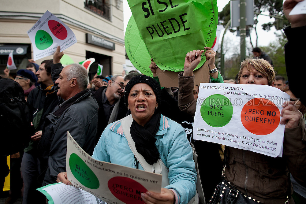 Anti-eviction activists hold placards and shout slogans after a 'escrache' outside the house of Popular Party Deputy Mari Luz Prieto, on April 4, 2013 in Madrid, Spain. Placard reads 'Yes we can, but they don't want'. The Mortgage Holders Platform (PAH) and other anti evictions organizations are organizing 'escraches' for several weeks under the slogan 'There are lifes at risk' to claim the vote for a Popular Legislative Initiative (ILP) to stop evictions, regulate dation in payment and social rent outside Popular Party deputies' houses and offices..'Escraches' are form of peaceful public protest that was used in Argentine in 1995 to point to pardoned genocides of Argentenia's Dictatorship within their neighborhoods.