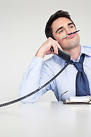 Businessman on phone balancing pen on upper lip