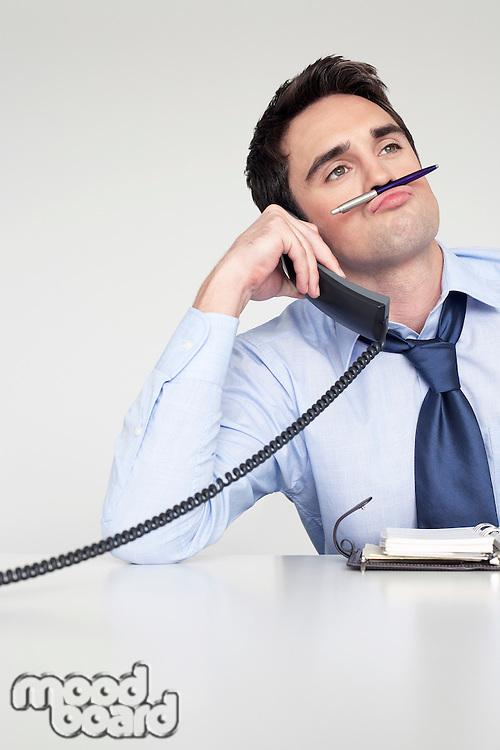 Businessman on phone balancing pen on upper lip