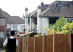 © Licensed to London News Pictures. 23/09/2011. LONDON, UK. A police officer guards the property. Six people, including three children, two teenagers and an adult have died following a house fire in Neasden, North West London today (24 Sept 2011). Emergency services were called tot he blaze in the early hours of the morning. Photo credit:  Stephen Simpson/LNP