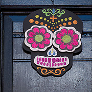 Day of the Dead  Symbol hanging outdoors  front door in Greenwich Village.<br /> <br /> Day of the Dead (Spanish: D&iacute;a de Muertos) <br /> <br /> The roots are pre-Colombian, and many of the symbols and practices are from indigenous groups of Meso America ( Maya and Aztec ).<br /> <br /> Day of the Dead is not a sad or scary occasion, but a spirited holiday when people remember and honor family member who have died. The philosophy that death is not something to be feared, but a natural part of life.<br /> <br /> Private and community altars called ofrendas, honoring the deceased display portraits, favorite foods and special possession of their love ones, using sugar skulls, marigolds, candles and the favorite foods and beverages of the departed, and visiting graves with these as gifts. Visitors also leave possessions of the deceased at the graves.