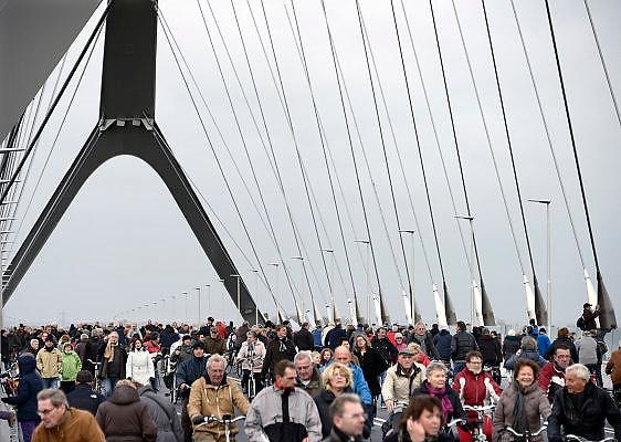 Nederland, Nijmegen, 24-11-2013Zaterdag is de nieuwe stadsbrug van de stad Nijmegen, de Oversteek, in gebruik genomen, geopend. Op de foto neemt het publiek op zondag de brug in bezit. Vanaf middernacht mag het autoverkeer over de brug rijden. Ongeveer 10.000 mensen liepen naar de andere kant en terug.  De brug is vernoemd naar de heldhaftige oversteek van de rivier de Waal die Amerikaanse soldaten op dit punt maakten tijdens de operatie Market Garden in de tweede wereldoorlog om met succes de oude Waalbrug te veroveren. De overspanning is een belangrijke schakel in de ontlasting van de stad van het doorgaande verkeerDe Oversteek is een boogbrug van 285 meter lang en 60 meter hoog en is de op een na langste hoofd overspanning van Nederland, en de grootste boogbrug van Europa met een enkelvoudige boog.De brug wordt 23 november in gebruik genomen.De nieuwe oeververbinding moet zorgen voor een betere spreiding en doorstroming van verkeer binnen de stad Nijmegen. Na 75 jaar is er eindelijk een tweede vaste verbinding voor de stad. De oude waalbrug krijgt vanaf eind dit jaar groot onderhoud, waarna de volle capaciteit van beide bruggen pas gebruikt kan worden. De skyline van de stad is veranderd.De brug is een ontwerp van de Belgische architecten Ney en Paulissen. Foto: Flip Franssen/Hollandse Hoogte
