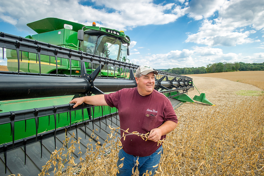 Farmer standing next to soybean harvester in Laytonsville, Maryland, USA