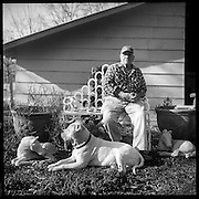 Marvin Fuquay sits with his dog on a bench made of horseshoes at his horse farm surrounded by objects that who his love for horses. Love, Mississippi
