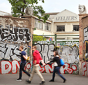 "Tourists passing through a grafitied entrance to a factory in a narrow street of Paris' famous Saint-Ouen flea market (marche aux puces de Saint Ouen) in the Paris neighbourhood suburb of Saint-Ouen, France.  Born in 1885, Saint-Ouen antique market, is the largest concentration of antique and second-hand dealers in the world. In 2001, Saint-Ouen antique market was classified ""Zone de Protection du Patrimoine Urbain et Paysager"". Picture by Manuel Cohen"