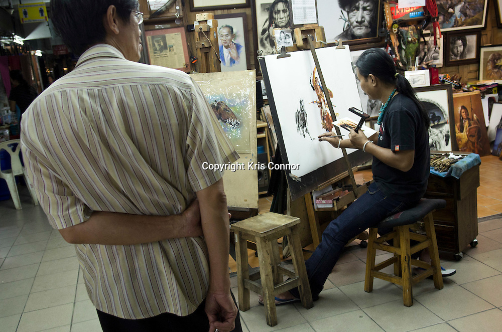 A man recreates a photo at a shop in the Night Bazaar district in Chiang Mai, Thailand. Photo by Kris Connor