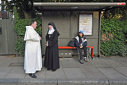 TWICKENHAM LONDON. Religious Pilgrims stand at a bus stop next to the entrance to St Mary's University. The Richmond Coalition Against the State Visit greet Pope Benedict XVI as he visits St Mary's University in Twickenham for a Celebration of Roman Catholic education. The Coalition oppose the Pope's opinions on condom use, abortion, gay rights and education. 17 September 2010. STEPHEN SIMPSON.