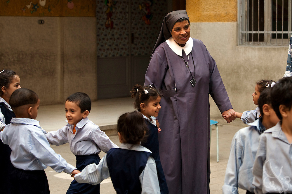 Sister Sara plays with children at the school for poor children  that she helped found more than 30 years ago with the famous French nun, Sister Emanuel in the Manshiyet Nasser district of the Egyptian capital, Cairo October 16, 2008. The school now provides an education to more than 1200 students from the surrounding slums which are a large garbage collection district.