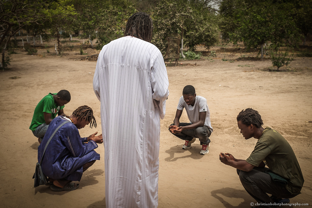 "Marabout Serigne Cheikh Seye prays with his Baye Fall disciples in the fields of ""Taw Feekh."" Submission to their spiritual leaders and teachers, whom they  call ""Marabout,"" is one the core values of the Baye Fall brotherhood and therefore part of fighting the Jihad."