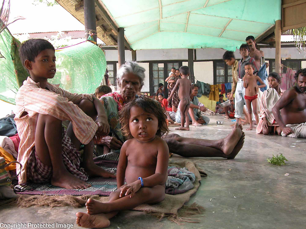 An unidentified flood victim 82- years old woman with his grandsons is sitting at Government Girl's Higher Secondary School relief camp at Dhubri district, about 293 km southwest of Gauhati, India, Wednesday, July 16, 2003 where devastated flood water of the river, Brahmaputra and its many tributaries submerged the village and town areas and affected more than 3 million people in 20 districts of  North East Indian state, Assam. (AP Photo/Shib Shankar Chatterjee)