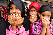 07 JULY 2013 - NARATHIWAT, NARATHIWAT, THAILAND:   Thai Muslim girls pray during a civil affairs project sponsored by Royal Thai Marines in Narathiwat Sunday. Royal Thai Marines in Narathiwat province held a special ceremony Sunday in advance of Ramadan. They presented widows, orphans and indigent people with extra rice and food as a part of the Thai government's outreach to resolve the Muslim insurgency that has wracked southern Thailand since 2004. The Holy Month of Ramadan starts on about July 9 this year. Muslims are expected to fast from dawn to dusk, engage in extra prayers, recitation of the Quran and perform extra acts of charity during Ramadan. It is the holiest month of the year for Muslims.  PHOTO BY JACK KURTZ