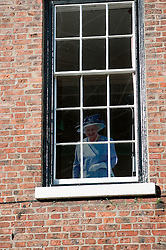 A cardboard cut out of the queen looks out over the City of York from an Upstairs Window during her Diamond Jubilee Year<br /> 11  May 2012.<br /> Image © Paul David Drabble