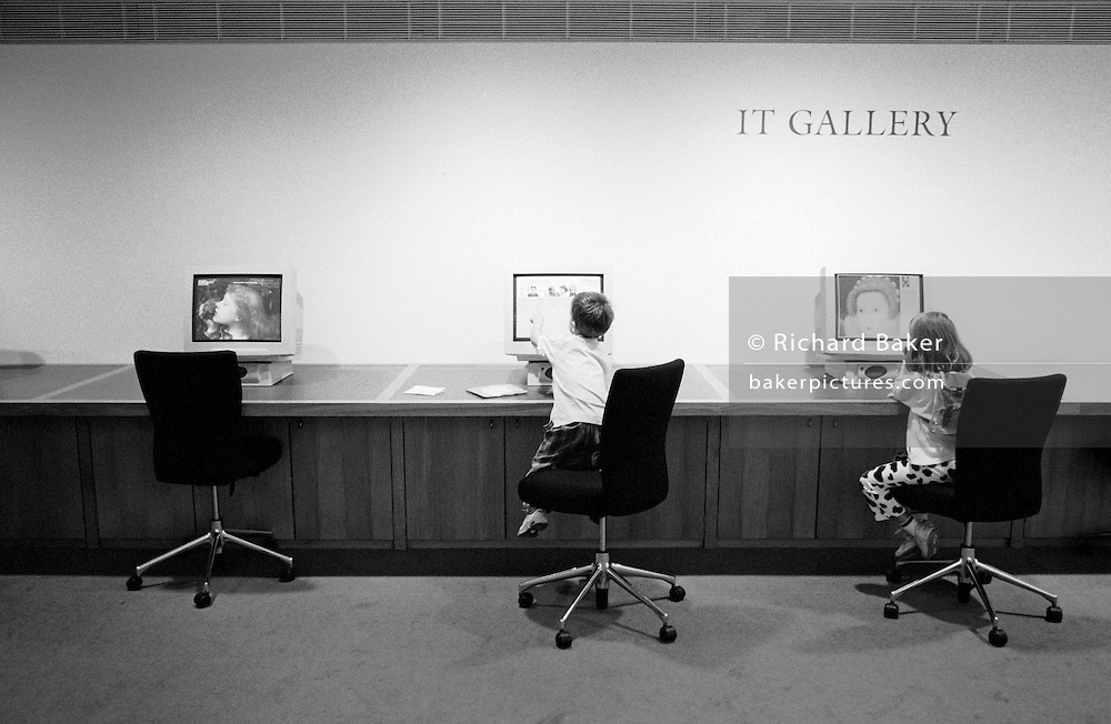 "Two children play on interactive computers in an upper floor of the National Portrait Gallery, the well-known art museum on Trafalgar Square in Central London. The institution's IT Gallery allows young users to search and discover for themselves great works of art from its extensive database including this image of the Tudor Queen Elizabeth I whose painted portraits are on view elsewhere: Her face seen on the far right screen. From a personal documentary project entitled ""Next of Kin"" about the photographer's two children's early years spent in parallel universes. Model released."