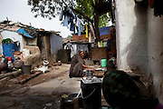 An overview of the family's shared compound as Sadma Khan's maternal aunt makes lunch in a slum area of Tonk, Rajasthan, India, on 19th June 2012. She was married at 17 years old to Waseem Khan, also underaged at the time of their wedding. The couple have an 18 month old baby and Sadma is now 3 months pregnant with her 2nd child and plans to use contraceptives after this pregnancy. She lives with her mother since Waseem works in another district and she can't take care of her children on her own. Photo by Suzanne Lee for Save The Children UK