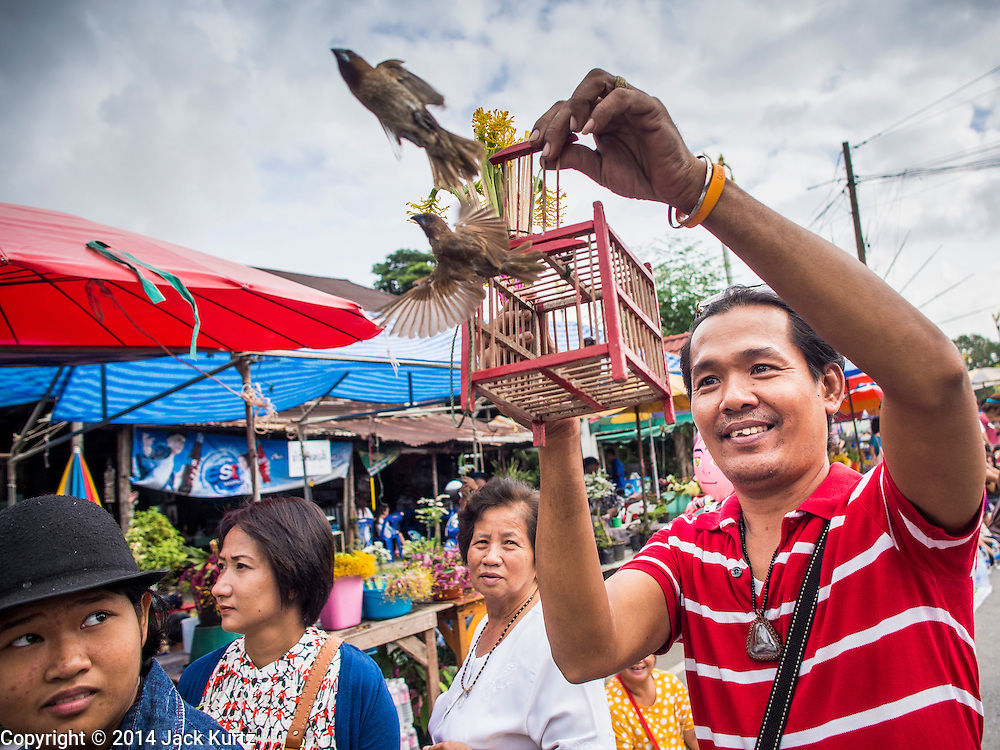 """12 JULY 2014 - PHRA PHUTTHABAT, SARABURI, THAILAND: A man makes merit by releasing birds before the Tak Bat Dok Mai at Wat Phra Phutthabat in Saraburi province of Thailand. Wat Phra Phutthabat is famous for the way it marks the beginning of Vassa, the three-month annual retreat observed by Theravada monks and nuns. The temple is highly revered in Thailand because it houses a footstep of the Buddha. On the first day of Vassa (or Buddhist Lent) people come to the temple to """"make merit"""" and present the monks there with dancing lady ginger flowers, which only bloom in the weeks leading up Vassa. They also present monks with candles and wash their feet. During Vassa, monks and nuns remain inside monasteries and temple grounds, devoting their time to intensive meditation and study. Laypeople support the monks by bringing food, candles and other offerings to temples. Laypeople also often observe Vassa by giving up something, such as smoking or eating meat. For this reason, westerners sometimes call Vassa """"Buddhist Lent.""""    PHOTO BY JACK KURTZ"""