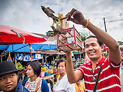 "12 JULY 2014 - PHRA PHUTTHABAT, SARABURI, THAILAND: A man makes merit by releasing birds before the Tak Bat Dok Mai at Wat Phra Phutthabat in Saraburi province of Thailand. Wat Phra Phutthabat is famous for the way it marks the beginning of Vassa, the three-month annual retreat observed by Theravada monks and nuns. The temple is highly revered in Thailand because it houses a footstep of the Buddha. On the first day of Vassa (or Buddhist Lent) people come to the temple to ""make merit"" and present the monks there with dancing lady ginger flowers, which only bloom in the weeks leading up Vassa. They also present monks with candles and wash their feet. During Vassa, monks and nuns remain inside monasteries and temple grounds, devoting their time to intensive meditation and study. Laypeople support the monks by bringing food, candles and other offerings to temples. Laypeople also often observe Vassa by giving up something, such as smoking or eating meat. For this reason, westerners sometimes call Vassa ""Buddhist Lent.""    PHOTO BY JACK KURTZ"