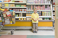 Young boy standing by fridge counter of supermarket