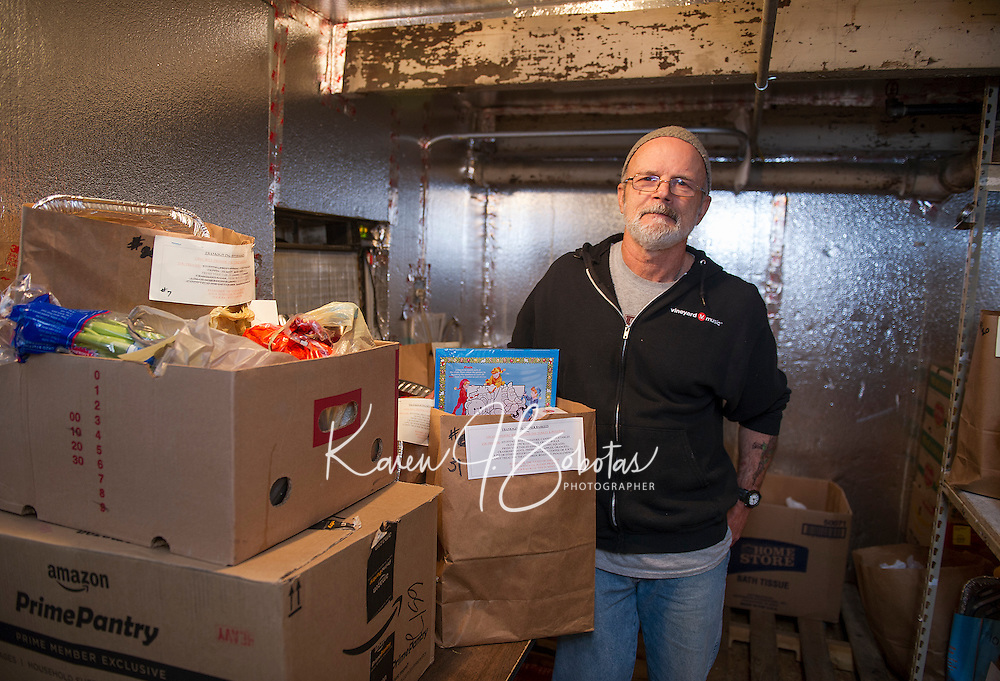 Pastor Dick AuCoin of the Lakes Region Vineyard Church readies Thanksgiving Baskets for those in need to be packed for delivery or pickup on Saturday.  (Karen Bobotas/for the Laconia Daily Sun)