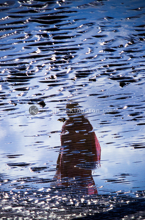 PORT BLAIR, ANDAMAN ISLANDS, INDIA,  The reflection of a woman clad in a sari in a tidal pool near Port Blair, India.