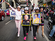 "14 JULY 2013 - BANGKOK, THAILAND:  Royalist supporters of the Thai monarchy carrying photos of Bhumibol Adulyadej, the King of Thailand, and his wife, Queen Sirikit, march in Bangkok Sunday. About 150 members of the so called ""White Mask"" movement marched through the central shopping district of Bangkok Sunday to call for the resignation of Yingluck Shinawatra, the Prime Minister of Thailand. The White Mask protesters are strong supporters of the Thai monarchy. They claim that Yingluck is acting as a puppet for her brother, former Prime Minister Thaksin Shinawatra, who was deposed by a military coup in 2006 and now lives in exile in Dubai.       PHOTO BY JACK KURTZ"