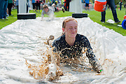 Bridget Mearns slides to the finish line on a slip and slide after finishing the Race for a Reason Mud Run. Photo by: Ross Brinkerhoff. Race for a Reason, Race 4 A Reason, Annual Events, Events, Students, Faculty & Staff