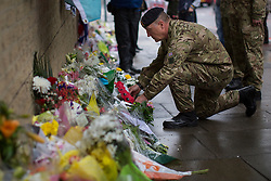 © licensed to London News Pictures. London, UK 28/05/2013. A group of military personnel lay a wreath and pay their respects at the scene where Drummer Lee Rigby was murdered by two men in Woolwich town centre in what is being described as a terrorist attack. Photo credit: Tolga Akmen/LNP