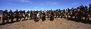 Mongolia. hunting with Eagle. Golden eagle festival in Kazakh province.  Bayan Ulgi.  The tournament participants come from all over Bayan Ulgii province in the extreme west of , near the Kazaksthan border. They arrive dressed in colorful apparel, fur coats and headgear made from wolfskins. Each trainer carries a hooded eagle on their forearm, it's claws firmly planted in a leather glove or  - bialai.  /  chasse à l'aigle  . festival des chasseurs avec Aigle doree, province Kazakh  Bayan Ulgi   .les particiapnts aux tournois arrivent de toute la province de Bayan Ulgii a l'extreme ouest de la Mongolie pres de la frontière avec le Kazaksthan.  Les cavaliers sont sur leur trente et un : habits d'apparat, dehls multicolores, manteaux de peaux, et chapeaux en fourrure de loup. Chacun tient un aigle encapuchonné, serres plantées dans un gant de cuir (le bialai), posé sur l'avant bras. Ce dernier est en appui sur un bâton sculpté arrimé à la selle. De l'autre, et d'une main, le cavalier tient les rênes