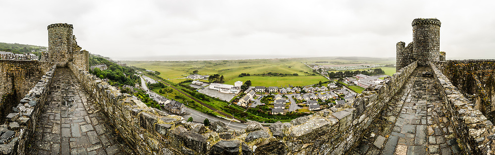 A wide panorama of castle ramparts looking towards the coastline of the Irish Sea from Harlech Castle in Harlech, Gwynedd, on the northwest coast of Wales next to the Irish Sea. The castle was built by Edward I in the closing decades of the 13th century as one of several castles designed to consolidate his conquest of Wales.