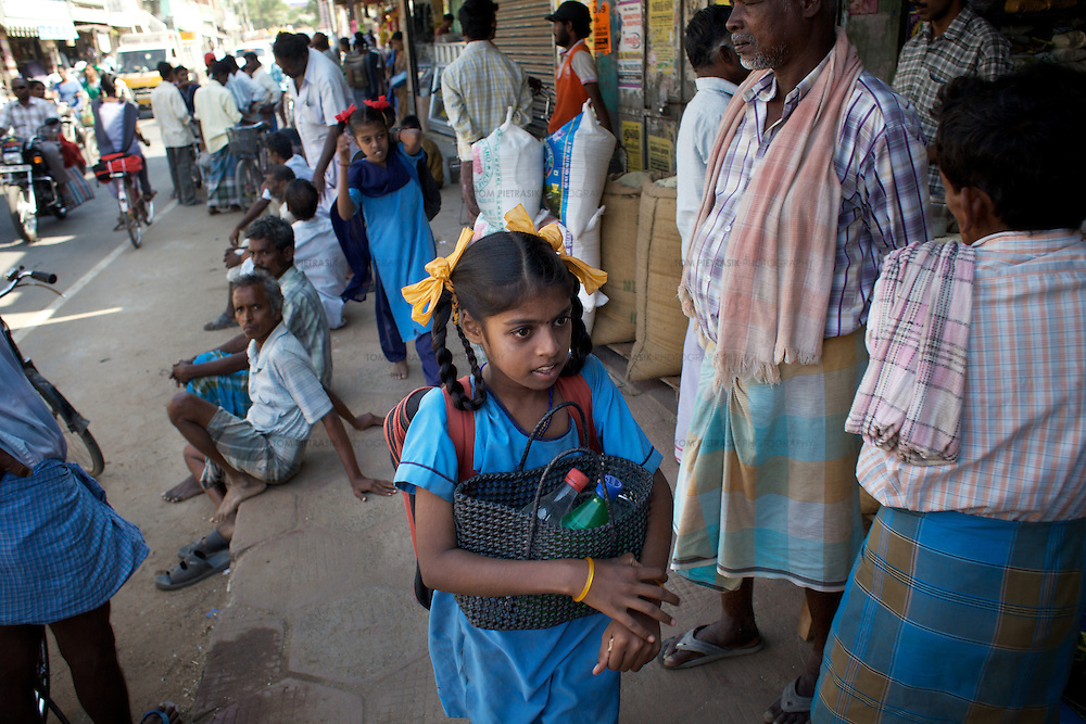 "Vijyashree (foreground) and Vijita on their way to school after catching a shared rickshaw from their home village of Thazanguda into Cuddalore...Vijita (age 14) and Vijyashree (age 11) Viswanathan lost their mother and brother to the tsunami in 2004. They continue to live in the fishing village of Thazanguda with their father Viswanathan, his second wife Kayalvizhi and their two children Sanjay (age 3) and Monica (age 1). ..Until the beginning of the 2009 academic year in June, Vijita and Vijyashree attended the local Thazanguda school. This village school teaches pupils only until the 8th Standard and with Vijita now entering the 9th, it was decided that the two daughters remain together and both travel 3km to the local town school: the Government Girls High School, Venugopalapuram in Cuddalore. ..At the same time Viswanathan decided he would cease day-to-day care of his daughters and place them in the Government Home for Tsunami Children, also in Cuddalore. This was not a move welcomed by either Vijita or Vijyashree and one afternoon after just two weeks at the orphanage, the two girls ran away. At roll call in the orphanage that evening the alarm was sounded and the two sisters were eventually located in Thazanguda waiting for their father and Kayalvizhi who were both away at the time. Realising his daughters' unhappiness, Viswanathan then took them out of the Government home. ..According to her class teacher, Vijita often compares her step-mother to her mother and concludes that she wants her mother back. Vijita confides in her teachers that her stepmother is forever demanding that she and her sister Vijyashree undertake housework. This frustration at home is tempered by the genuine love both sisters have for their father and two younger siblings Sanjay and Monica. Vijita expresses a lonelyness without her mother. Pushpavalli concludes that ""Vijita wants something else beyond the love of her father and sister"". ..Viswanathan appears genuinely to want the best f"