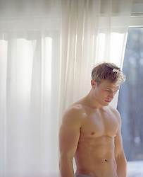 shirtless blond man at home in deep thought