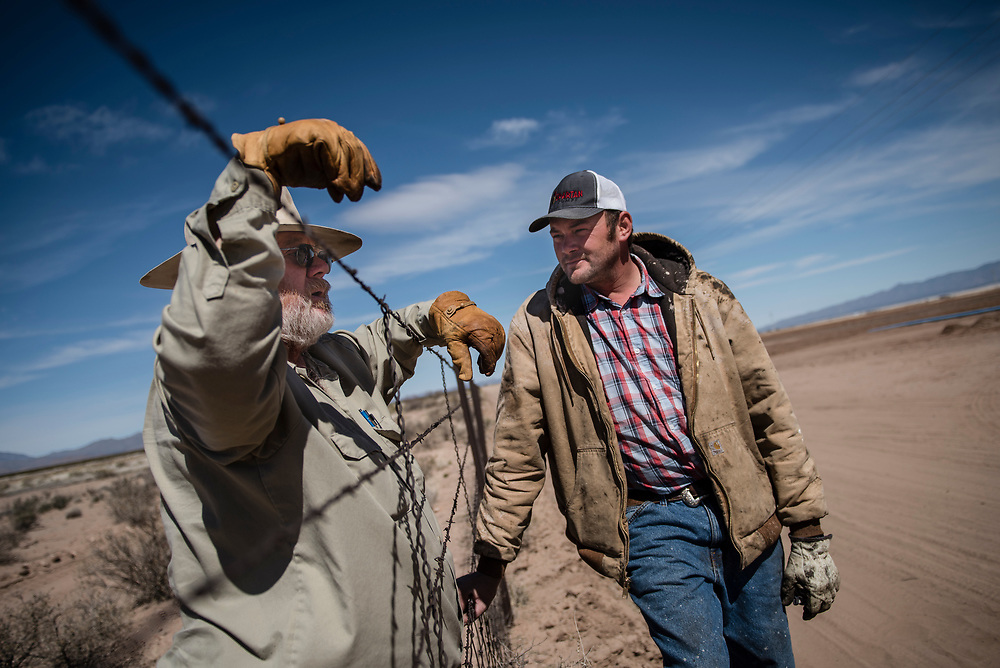 rer031617b/A1/03.16.17/Roberto E. Rosales<br /> William Hurt(Cq) is a private landowner and leaseholder who lives, ranches and farms along the U.S.-Mexico border in New Mexico's bootheel area. Hurt feels he should be consulted before any construction of a wall would be built on his land.  Pictured is Williman Hurt (Cq) on the left. leaning on a barb wire fence that makes up the U.S-Mexico border talking to David Fehr(Cq) who stands on the Mexican side of the fence as they discuss farming. <br /> Hachita New Mexico. ( Roberto E. Rosales/Albuquerque Journal.)
