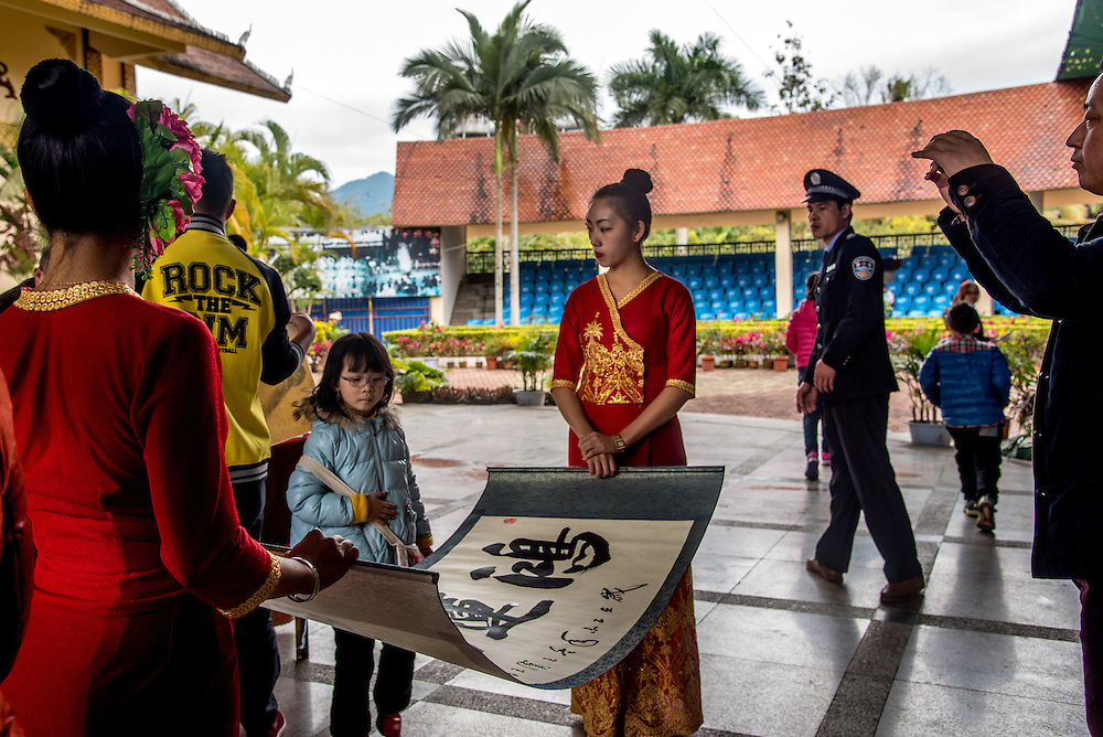 A Chinese caligraphy demonstration for tourists at the Olive Dam Dai cultural village in Xishuangbanna, China. The Dai are an ethnic minority living in western China as well as northern Laos, Thailand, and Vietnam.