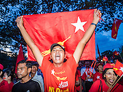 01 NOVEMBER 2015 - YANGON, MYANMAR:  NLD supporters run through the streets of Thuwunna, a Yangon suburb, after the NLD's last election rally of the 2015 election was held in an empty field in Thuwunna Sunday. Political parties are wrapping up their campaigns in Myanmar (Burma). National elections are scheduled for Sunday Nov. 8. The two principal parties are the National League for Democracy (NLD), the party of democracy icon and Nobel Peace Prize winner Aung San Suu Kyi, and the ruling Union Solidarity and Development Party (USDP), led by incumbent President Thein Sein. There are more than 30 parties campaigning for national and local offices.   PHOTO BY JACK KURTZ