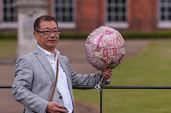 © Licensed to London News Pictures. 03/05/2015. London, UK. A tourist from China poses with a balloon tied to a railing outside the Golden Gates at Kensington Palace for the new daughter of the Duke and Duchess of Cambridge who was born the previous day. Photo credit : Stephen Chung/LNP
