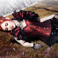 girl in victorian dress sitting on grass, looking sad and thoughtfull